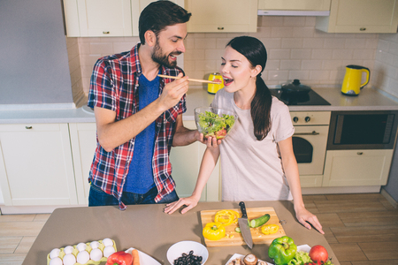 Cute picture of man standing at table and holding bowl with salad. He is stretching hand with wooden spoon with tomato on it. Girl opens her mouth. She wants to taste it.