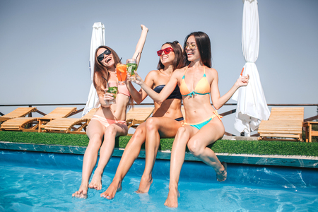 Happy and positive young women sit at edge of swimming pool. They stretch their bodies and cheer. Women are excited.