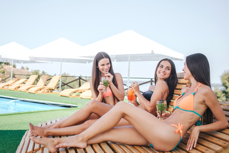 Three models sitting and lying on sunbeds. They chill. Young women drink cocktails and have rest. Models look at each other. They spend time together.