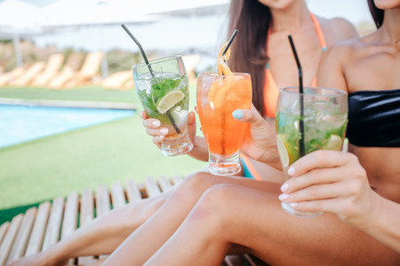 Cut view of three beautiful women sit on sunbeds and hold cocktails in hands. There are two green and one orange. Models cheer to relaxation and good rest.