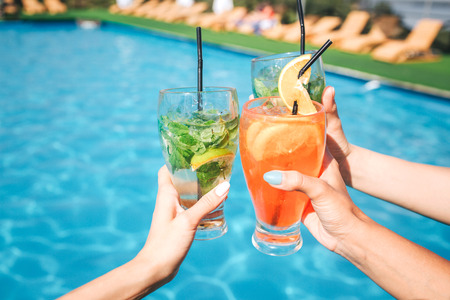 Picture of womens hands hold three glasses of cocktails in front of pool. There are two green and one orange drinks. Women keep glasses together.