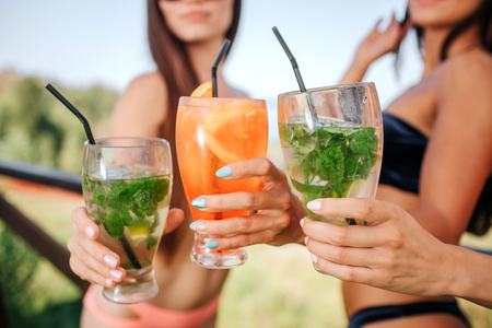Cut view of three models stands and hold three glasses with cocktails. There are one orange and two green colored drinks. Young women keep them together.