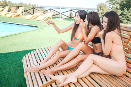 Three models sits on sunbeds. Two of them are gossiping. Woman on the left points forward. Model in the middle is leaning to the first one. They have rest.