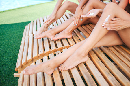 Cut view of slim and well-build young womens legs. They have tan. Hands put some sun protection lotion on legs. Models sit on sunbeds. Stock Photo