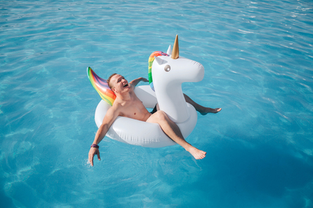 Happy young man sits in white float and enjoy. He smiles and keeps eyes closed. Guy is in pool alone.