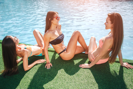 Three delightful models sit on grass at edge of swimming pool. One gets tan from sun. Other two look at each other and smile. Young women have fun. They relax.