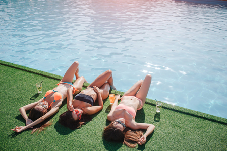 Three models are lying on grass. They holds legs in water and get tan from sun. Models stratching and sleeping. They are relaxed and calm.