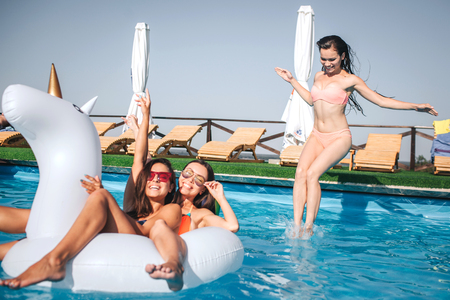 Two girls swimming on white float. They cilling and having rest. Third one jumps in water. She looks down. Other two models pose on camera. Stock Photo