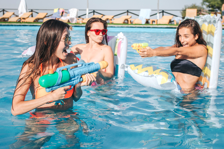 Picture of models playing and having fun in swimming pool. They have fight. Young woman shooting into each other with water gun. Sexy models have a good game.