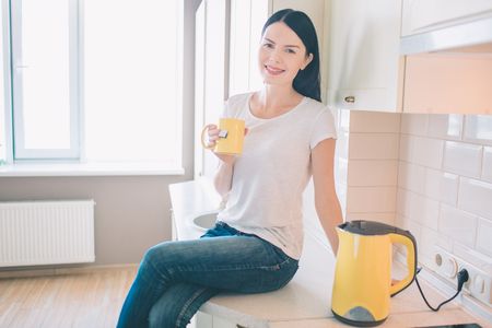Nice and positive woman sits on curbstone and looks on camera. She poses and smiles. Woman holds yellow cup in hands. Also she sits at kettle.