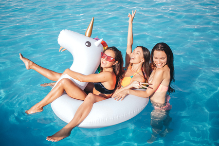 Funny and gorgeous young woman swimming in pool. They play with white float. Two models are there. Third one is behind them. Young models have fun.