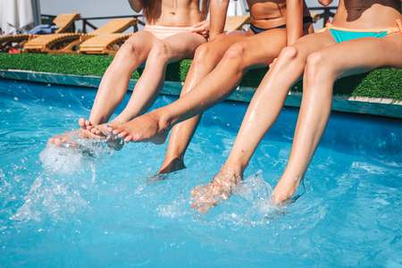 Picture of womans legs in middle splashing water in swimming pool. Other tow models are calm and peaceful. They chill and relax.