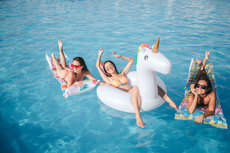 Picture of model are sitting and lying on floats in pool. They having rest. Two women lying on stomach and show their beautiful bodies. Model in middle stretching hands up and smiling 写真素材