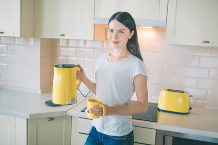Brunette stands in kitchen and looks on camera. She poses. Young woman holds yellow kettle and cup. There is a toaster standing besides her. Woman looks very nice.