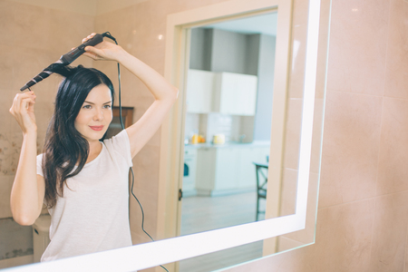 Brunette stands at mirror and using curler hair. She is in bathroom. Woman holds curler with both hands. She makes hair dressing. Stock Photo