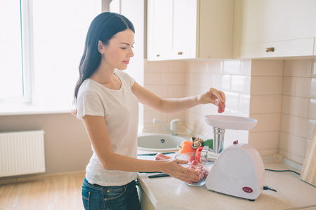 Nice young woman stands in kitchen. She grindes meat. There is a bowl with raw vegetables besides her.