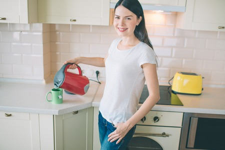 Positive young woman stands in kitchen and looks on camera. She pours hot water from red with blue kettle into cup. Woman smiles. She looks happy.