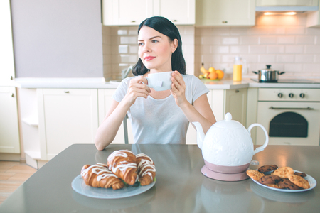 Dreamy woman sits at table and looks to right. She holds white cup in hands. There are kettle and plates with cookies and croissans at table.