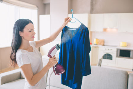 Woman is steaming blue shirt in room. She holds small stream iron in hand. Brunette is concentrated on work. Standard-Bild