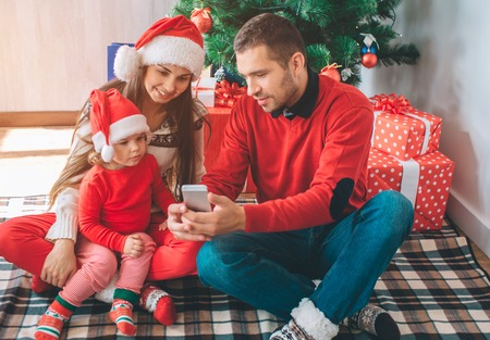 Merry Christmas and Happy New Year. Nice family sits together at Christmas tree. Man holds phone in hands and shows it to woman and child. They are concentrated. Girls wear red Christmas hats.
