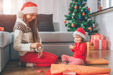 Merry Christmas and Happy New Year Positive and playful young woman and girl sit on floor. They smile and laugh. Child holds part of tape while woman has rest . They wear hats. Girls prepare gifts.