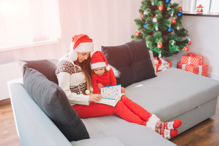 Merry Christmas and Happy New Year. Young woman sit on sofa with daughter. She holds book with pictures on her lap. Woman is reading. Girl listen. They look calm ad peaceful.