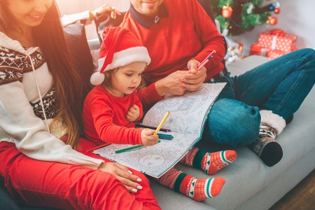 Merry Christmas and Happy New Year. Cut view of parents sitting on sofa with their child. Kid holds colouring and pencils on it. Girl draw with it. Young man holds some pencils too.