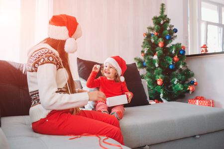 Merry Christmas and Happy New Year. Picture of happy kid sitting on sofa and hold white small round sweet. She looks at mother and smiling. Woman with long hair look at child. She is careful.
