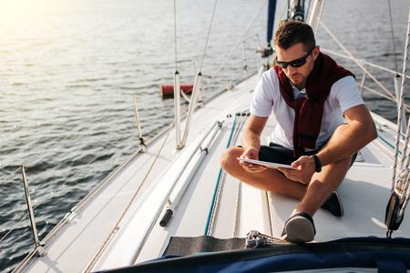 Ernstige en vreedzame man zit aan boord van jacht. Hij houdt vast en kijkt naar de tablet. Jonge man is kalm. Hij draagt witte sirt en donkere trui met korte broek.