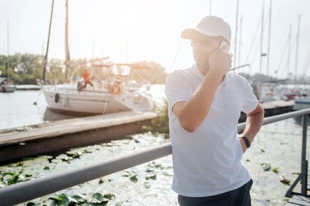 Busy young man stands on pier and look to left. He talks on phone. There are yachts behind him. Sun goes down. Guy is waiting.