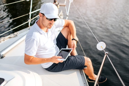 Picture of young man sits at edge of yacht board and hold tablet. It has dark screen. Man wears sunglasses and white cap with shirt. He is serious and confident. Sailor get some rest. Imagens