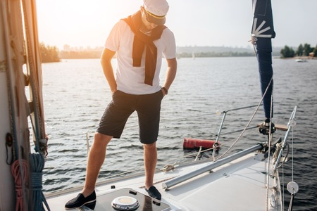 Another picture of oyung man stands on yacht. Hr keeps hands in pockets and look down. Young man has sweater on shoulders and cap on head. Also there are white shirt and dak short on his body. He poses.