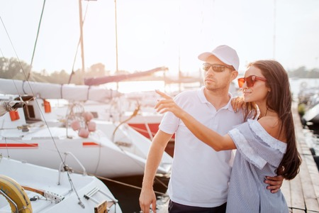 Beautiful and confident couple stands on pier and hug each other. They stand very close. Girl point with finger. They look in one direction. Young man is serious. Both of them wear sunglasses. 写真素材