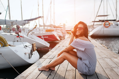 Wunderschönes Modell sitzt auf Pier und lächelt. Sie posiert. Junge Frau hält die Beine zusammen und hält die Haare mit der Hand vom Winken. Sie sieht glücklich aus. Standard-Bild
