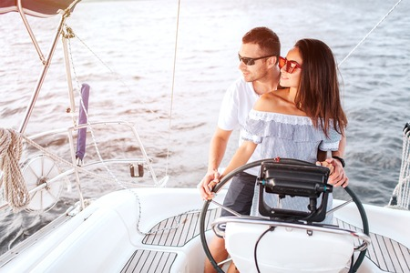 Couple stands together and look to left. She keeps hands on rudder. Guy has one hand there too. They wear dark and red sunglasses. Фото со стока