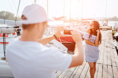 Picture of young man stands on pier and taking pictures of brunette. She poses on camera. Young woman looks to left. There are lots of yachts. Sun goes down. Фото со стока