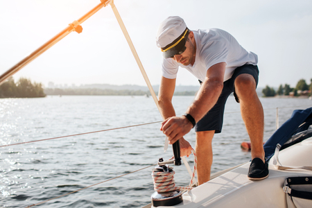 Picture of sailor stands on yacht and winds rope around. He is calm and concentrated. Young man works hard. He prepares for sailing. Stock Photo