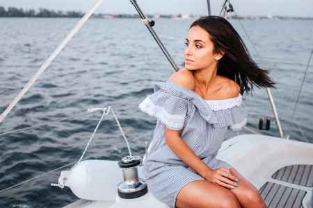 Amazing and beautiful young woman sitting on board of yacht and look to left. She is calm and peaceful. Woman is alone. Imagens