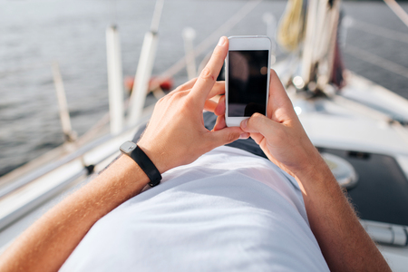 Picture of phone in mans hands. He holds in confident. Screen is dark. Phone is white. Young man lies on yacht board