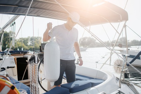 Serious sailor stands on his yacht and looks down. He holds rope with big plastic bottle. Young man is calm and peaceful. Sun goes down.
