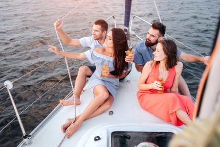 First couple sitting on bow of yacht and look on sunset. They hold on ropes and look to left. Another couple is doing the same thing. They enjoy time.
