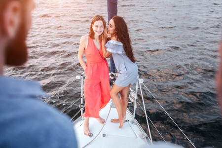 Beautiful young women stand together and pose. They wispering and laughing. Men stands adn look at them. Women are on bow of yacht. Stockfoto