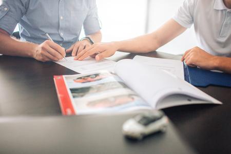 Zwei Männer sitzen am Tisch. Kerl auf der linken Seite, der Papiere unterschreibt, während der Mann auf der linken Seite mit der Hand zeigt. Vor ihnen liegt ein aufgeschlagenes Tagebuch. Es gibt auch kleines weißes Autospielzeug.