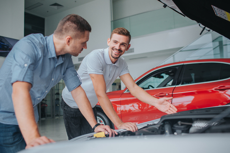 Seller in white sirt stands at opened body of car and point on it. He looks at guy and smiles. Man in grey shirt leans on car and looks at seller. Archivio Fotografico