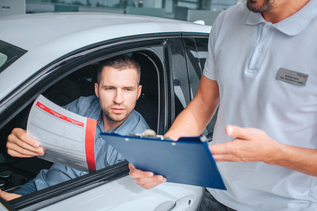 Seller stands at white car and holds tablet in hands. He point on it. Another man sits in car and holds insurance paper.