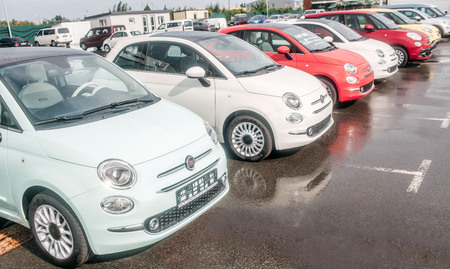 Picture of small and beutiful fiat cars standing outside on parking lot. There are red and white cars. Asphalt is wet underneath wheels. Editorial
