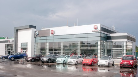 Picture of Fiat dealer salon with cars outside of it. There are cars with different colors of body. It is cloudy outide. Asphalt is wet because of rain.