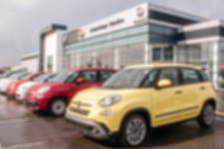 Unclear picture of Fiat cars standing outside close to dealer building. There is yellow car in front of picture. Red and white ones are behind it. It is cloude outside.