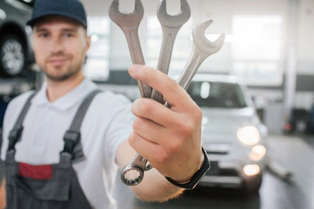 Young handsome man shows set of wrenches. He looks at them and smile. Guy wears uniform. He stands in front of white car. Young man smiles a bit.