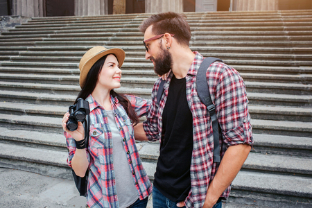 Young and positive man and woman stand in front of stairs and look at each other. They smile. People wear similar shirts. Woman holds black binoculars. 写真素材